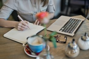 person-writing-on-a-notebook-beside-macbook-1766604